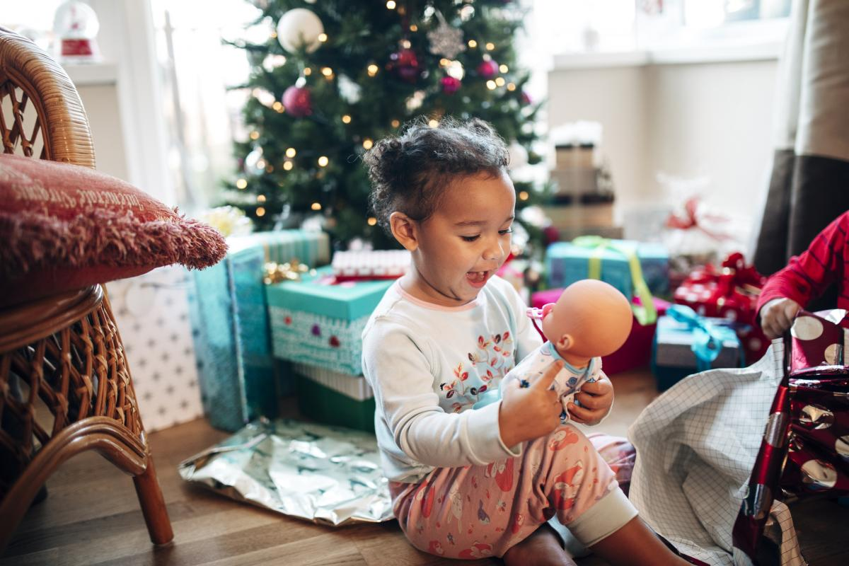 girl with baby doll and Christmas tree